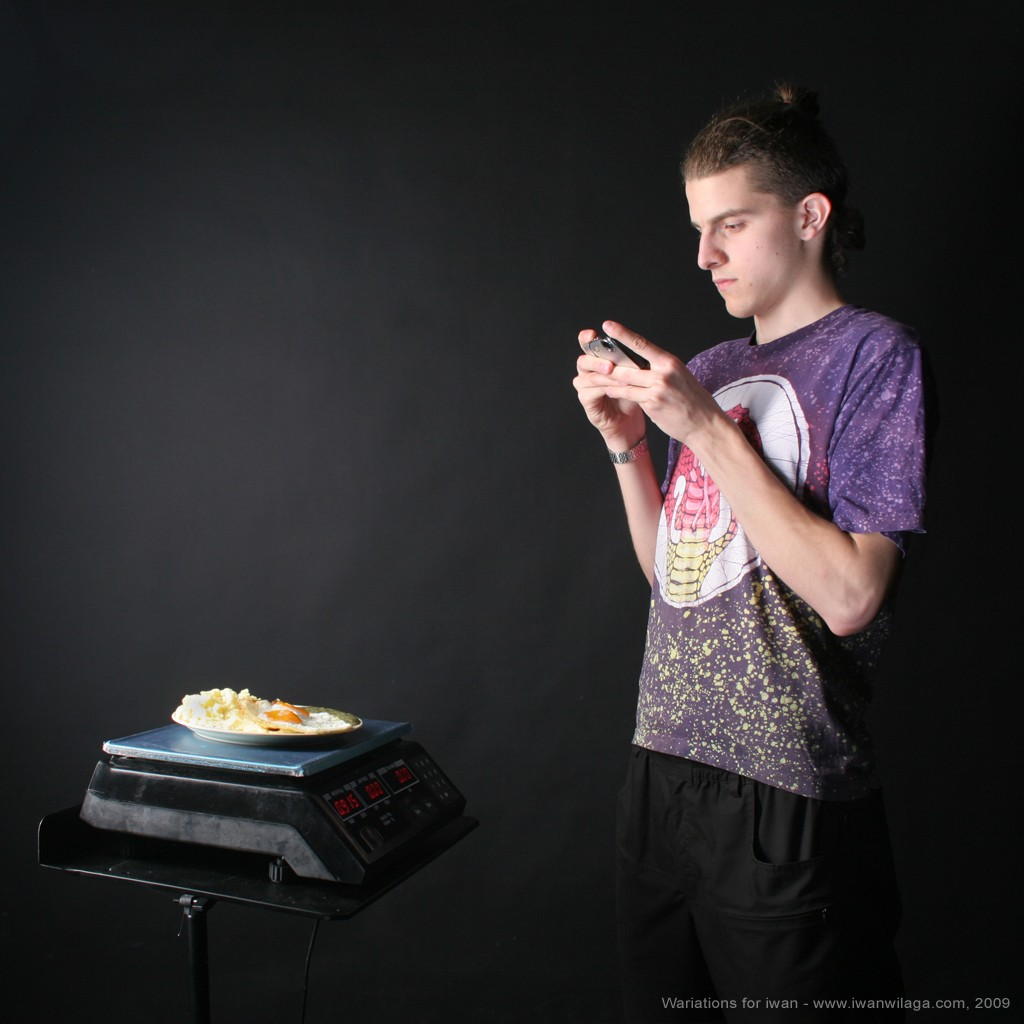 iwan is taking a digital picture of a meal, he tend to eat up from a digital weight scale.